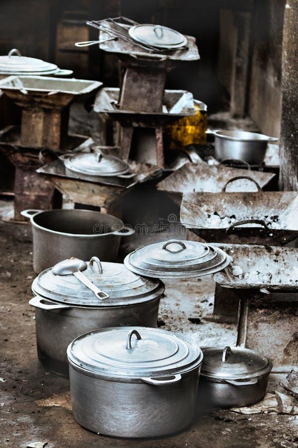 Rustieke houtskoolfornuizen en cookware, potten en pannen op de vloer bij de lokale markt van Toliara, Madagascar stock afbeelding