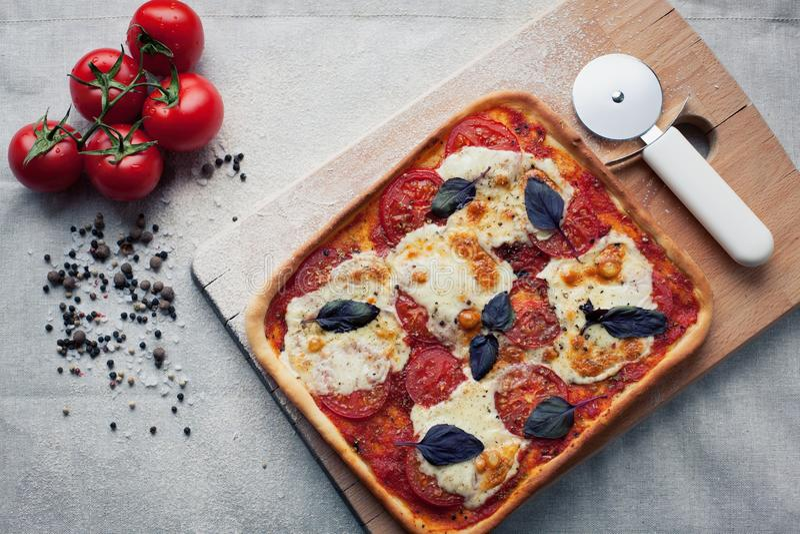 Rustieke Italiaanse pizza met mozarella, kaas en basilicumbladeren stock fotografie