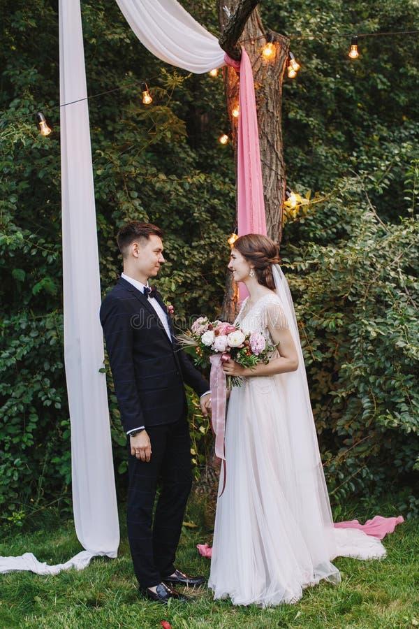 Rustieke openlucht het huwelijksceremonie van de avondzomer De bruid en bruidegomholdingshanden en zien elkaar stock foto