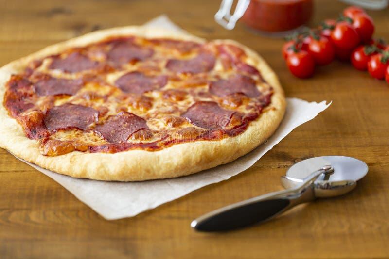 Rustieke pizza met salami, mozarella, olijven en basilicum royalty-vrije stock foto's