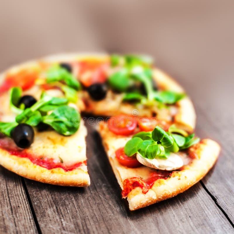 Rustieke pizza met salami, mozarella, olijven en basilicum hoogste mening stock foto's