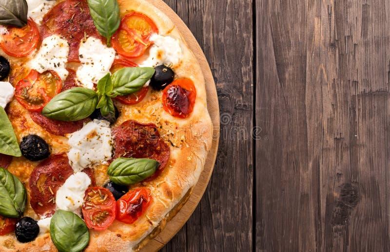 Rustieke pizza met salami, mozarella, olijven en basilicum op houten stock foto