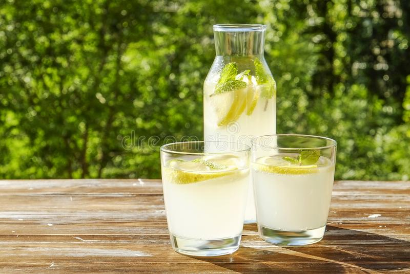 Rustieke samenstelling met vers gedrukte eigengemaakte koude limonade in fles en glazen met condensatiedruppeltjes royalty-vrije stock foto