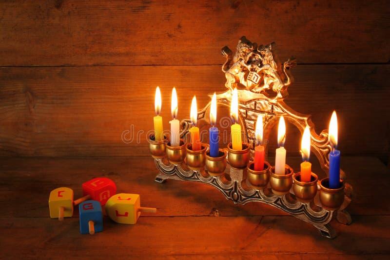 Rustig beeld van Joodse vakantiechanoeka met menorah (traditionele Kandelabers), donuts en houten dreidels (tol) stock foto's