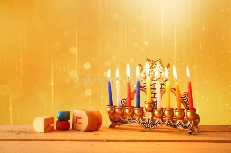 rustig beeld van Joodse vakantiechanoeka met menorah (traditionele Kandelabers) en houten dreidels (tol) schitter backgro stock fotografie