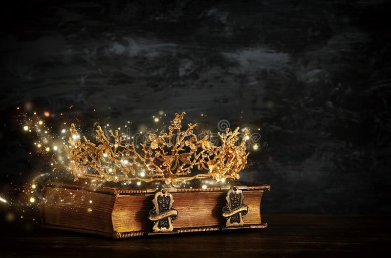 rustig beeld van mooie koningin/koningskroon op oud boek Gefiltreerde wijnoogst fantasie middeleeuwse periode stock foto
