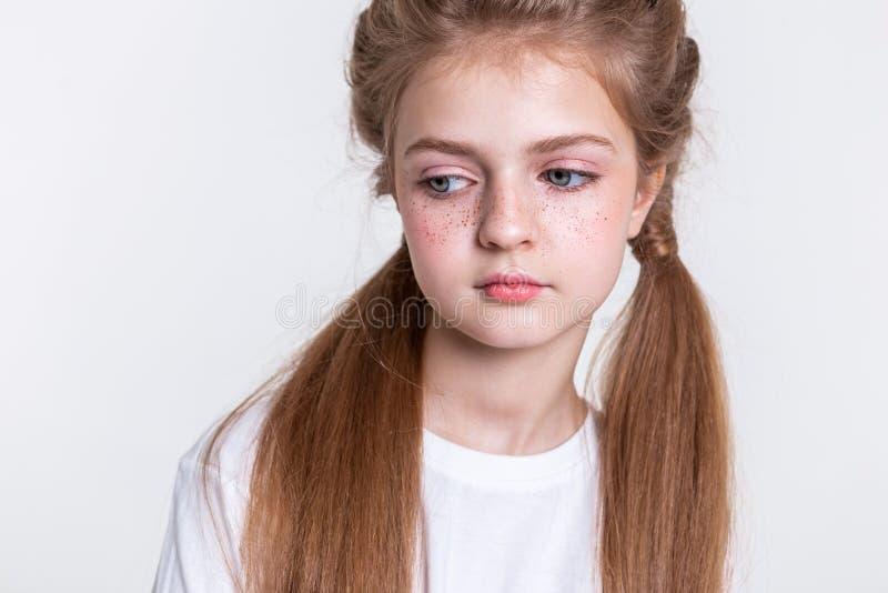 Rustig licht-haired meisje met twee lange staarten die duidelijke witte t-shirt dragen stock afbeelding