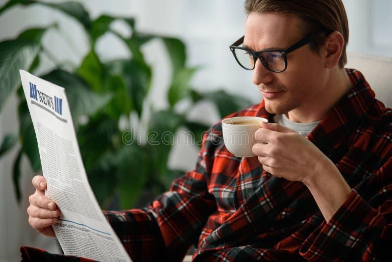Rustig volwassen mannetje die door de krant binnen kijken stock foto