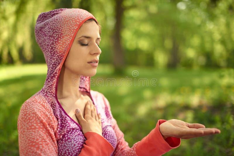 Rustige en vreedzame vrouw die bedachtzame voorlichtingsmindfulness uitoefenen door in aard te mediteren bij zonsondergang royalty-vrije stock fotografie