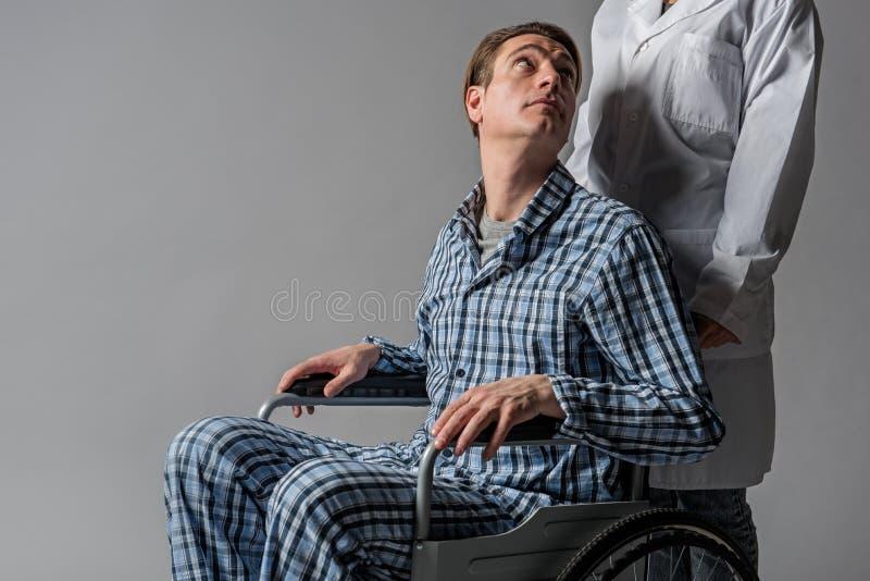 Rustige gehandicapte mens die bij verpleegster staren stock foto's