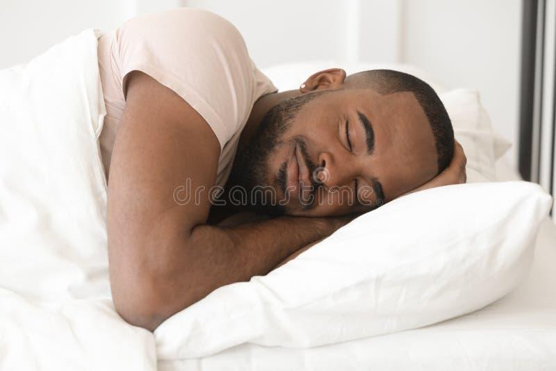 Rustige kalme jonge zwarte mensenslaap goed alleen in bed royalty-vrije stock afbeeldingen