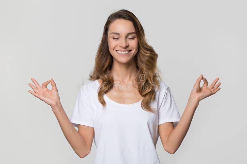 Rustige kalme vrouw die yogaoefeningen op witte lege achtergrond doen stock foto