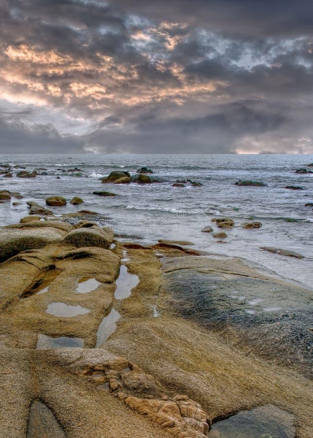 Rustige kust met rotsen vlak v??r een onweer, Hainan-Eiland, China royalty-vrije stock afbeelding