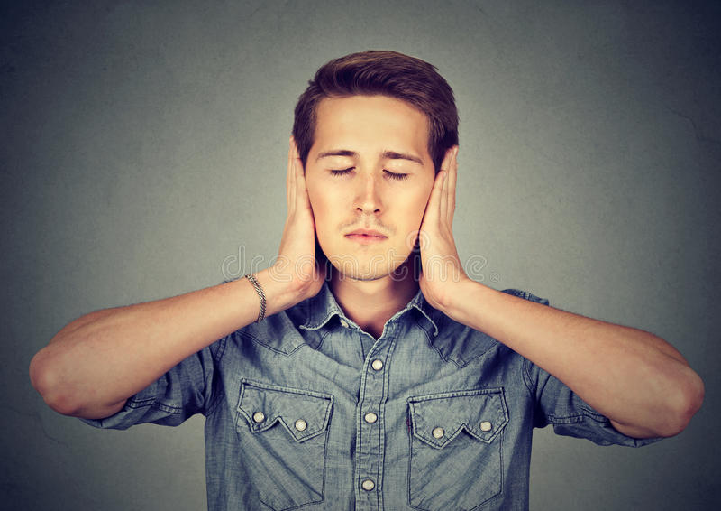 Rustige, ontspannen jonge mens die oren, gesloten ogen behandelen stock afbeelding