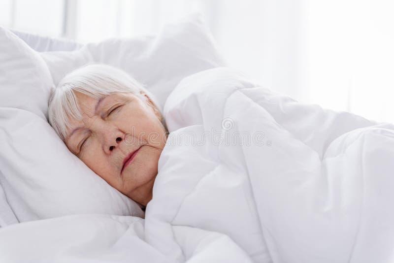 Rustige oude vrouw die aan bed in het ziekenhuis houden stock foto