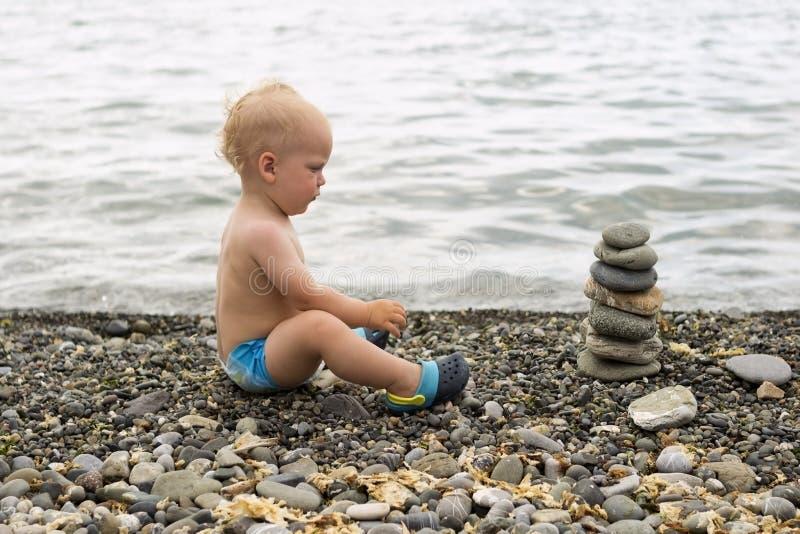 Rustige peuter die op het overzeese strand mediteren Leuke babyjongen die en aan de steenpiramide ontspannen kijken royalty-vrije stock fotografie