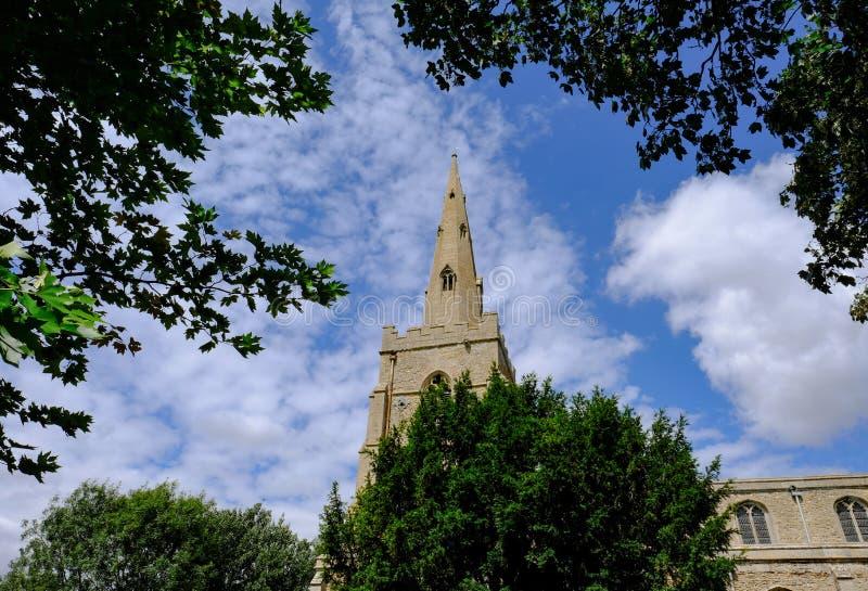 Rustige scène van een oude Engelse kerk en gezien die spits tegen nabijgelegen bomen en struiken wordt een ontworpen stock afbeeldingen