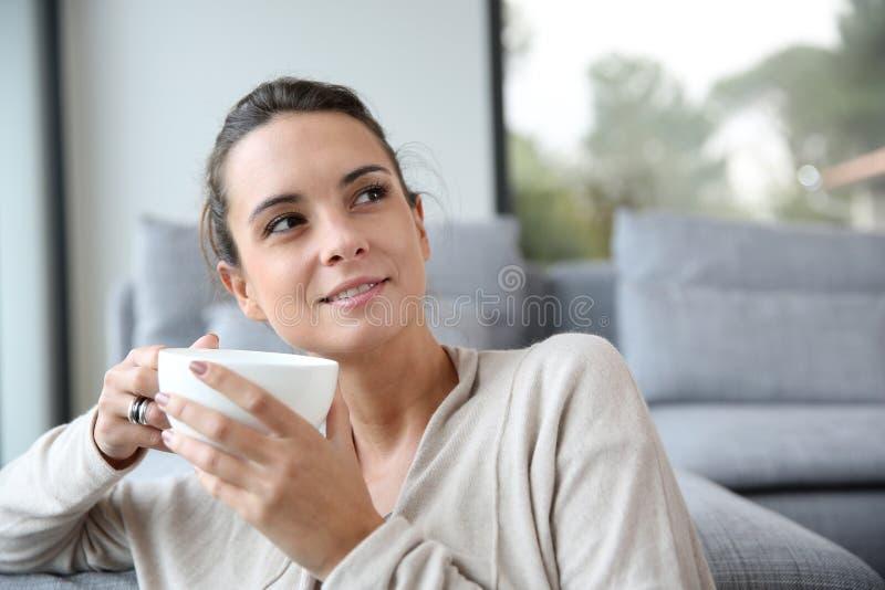 Rustige vrouw met kop thee thuis stock foto's