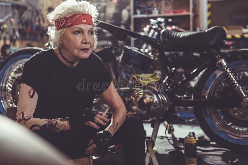 Rustige vrouwelijk trekt fuming dichtbijgelegen motorfiets terug royalty-vrije stock afbeeldingen