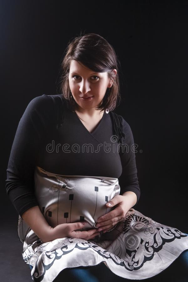 Rustige Zwangere Kaukasische Vrouw in het Steunen van Kleding Het zitten tegen Zwarte Achtergrond royalty-vrije stock fotografie