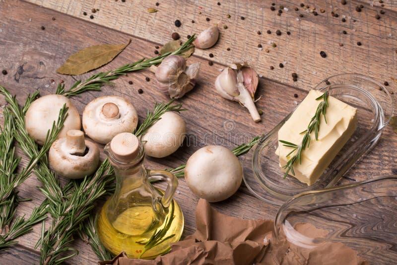 Rustikale Bestandteile und Champignons auf einem Holztischhintergrund Butter und Gewürze Flasche Öl Mahlzeiten mit Pilzen lizenzfreie stockfotografie