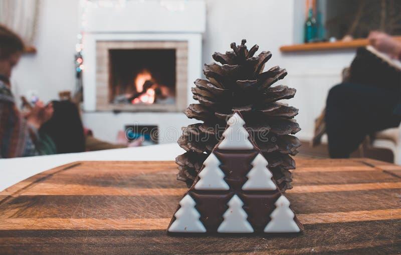rustikale Dekorationen der Winterweinlese mit Kiefernkegel und Weihnachtsbaumschokolade stockbilder