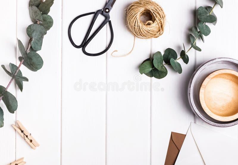 Rustikale Gegenstände und Eukalyptusniederlassungen auf der weißen Tabelle lizenzfreies stockbild