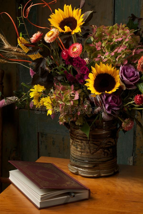 Rustikale noch Lebensdauer mit Herbstblumen und -buch lizenzfreies stockfoto
