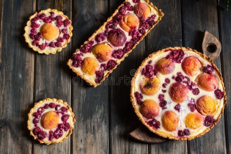 Rustikale offene Torte mit Pfirsich und Himbeere, französisches galette Pfirsichtörtchen Selektiver Fokus Tartalette mit Sahne Vi lizenzfreie stockfotografie