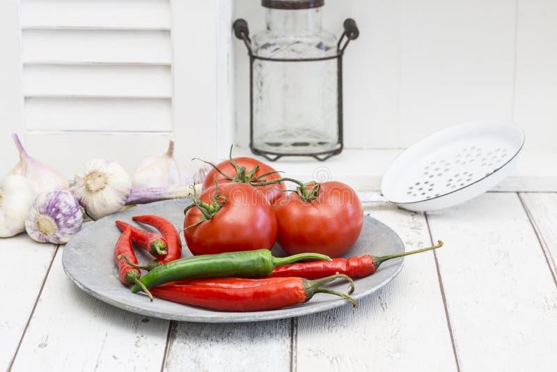 Rustikale Platte mit roten Tomaten und heißes kühles über weißem Küchen-Bereich stockbilder