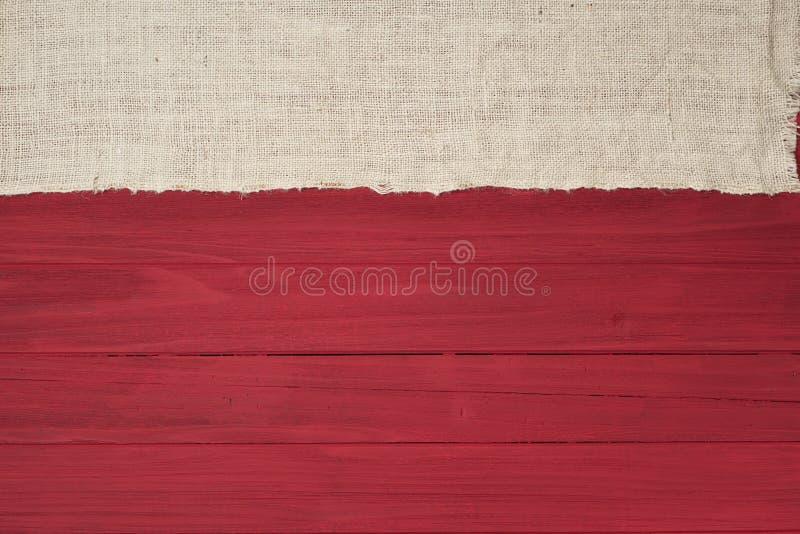 Rustikale rote hölzerne Bretter im flachen Plan mit weg weißem Leinwandgewebe auf Oberseite als dekorativem Gestaltungselement Es stockfotografie