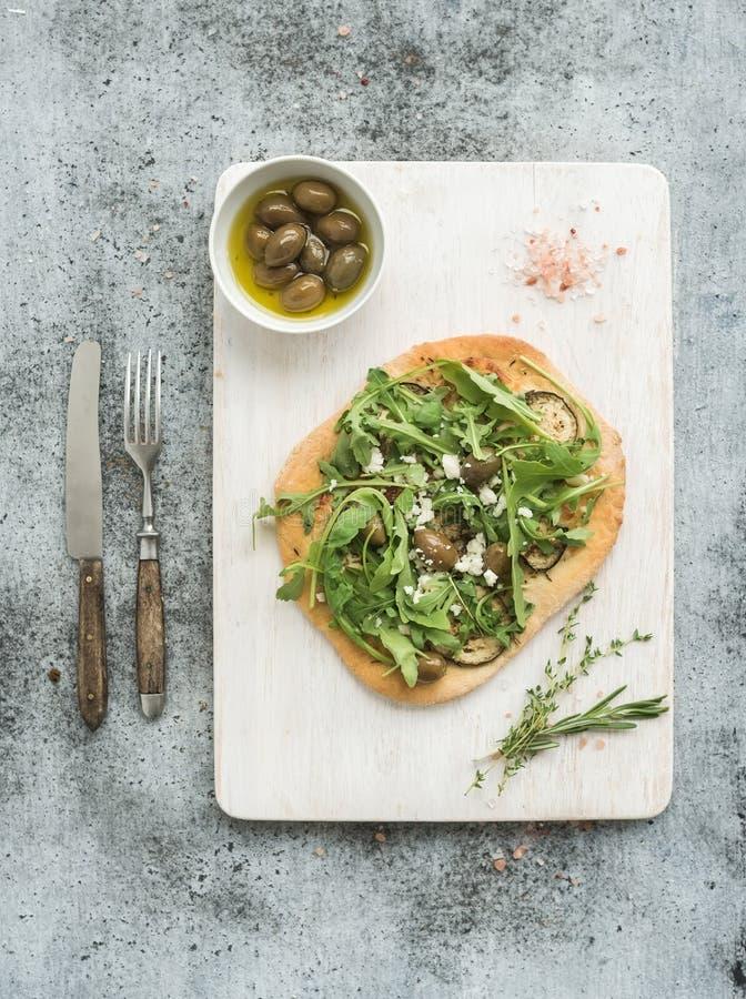 Rustikale selbst gemachte Pizza mit eggpant, Käse, Oliven und Arugula auf weißer hölzerner Umhüllung verschalen über grauem Schmu lizenzfreie stockbilder