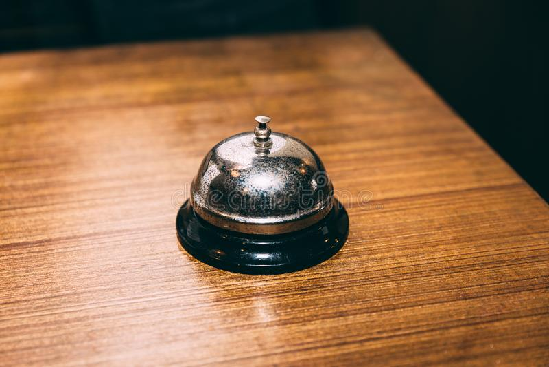 Rustikale Tischglocke oder Notklingel auf Holztisch Für das Anrufen des Kellners lizenzfreies stockfoto