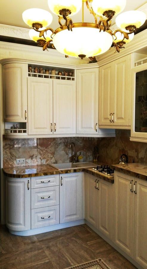 Rustikale weiße Küche mit einer großen Lampe stockfotografie