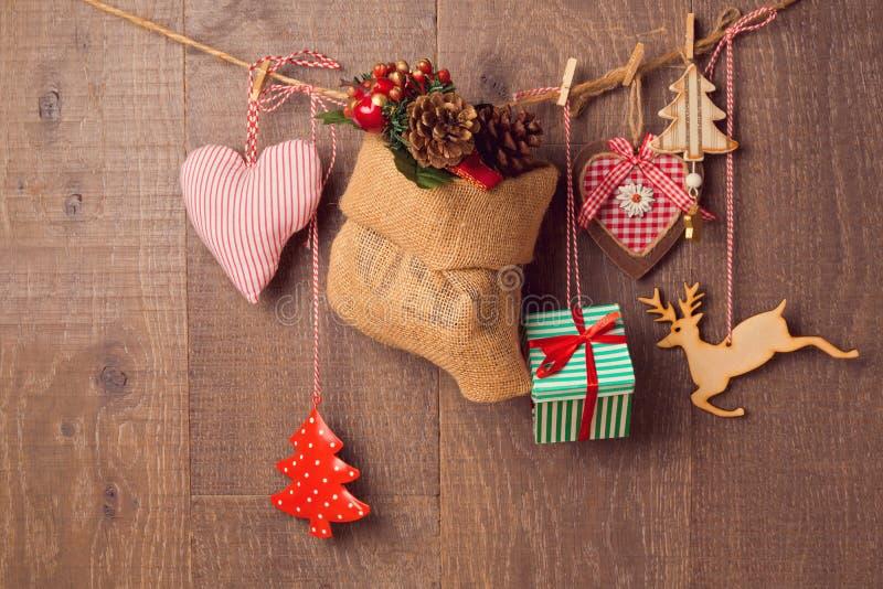 Rustikale Weihnachtsdekorationen, die über hölzernem Hintergrund hängen lizenzfreies stockfoto