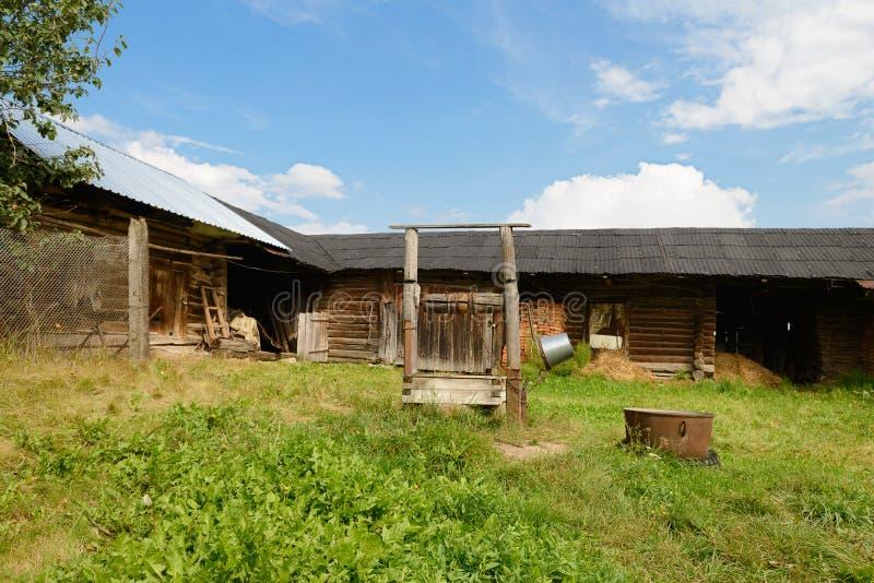 Rustikaler alter verlassener Hof mit einem Brunnen stockbild