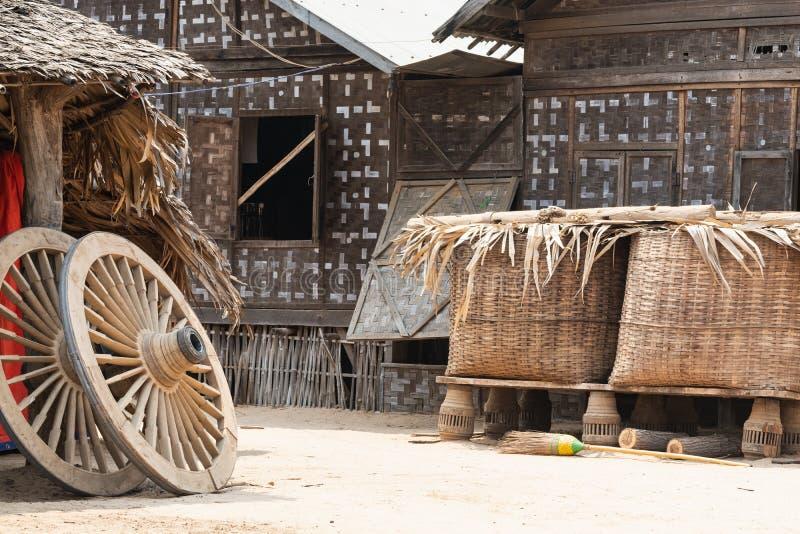 Rustikaler Hinterhof mit Bambushütte, Körben und zwei hölzernen Rädern lizenzfreie stockbilder