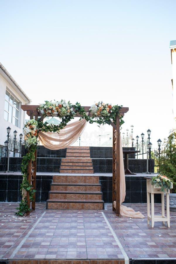 Rustikaler Hochzeitsbogen Hochzeitsbogen gemacht vom hölzernen quadratischen Rahmen, von den beige Stoff-, weißen und Orangeblume stockfoto