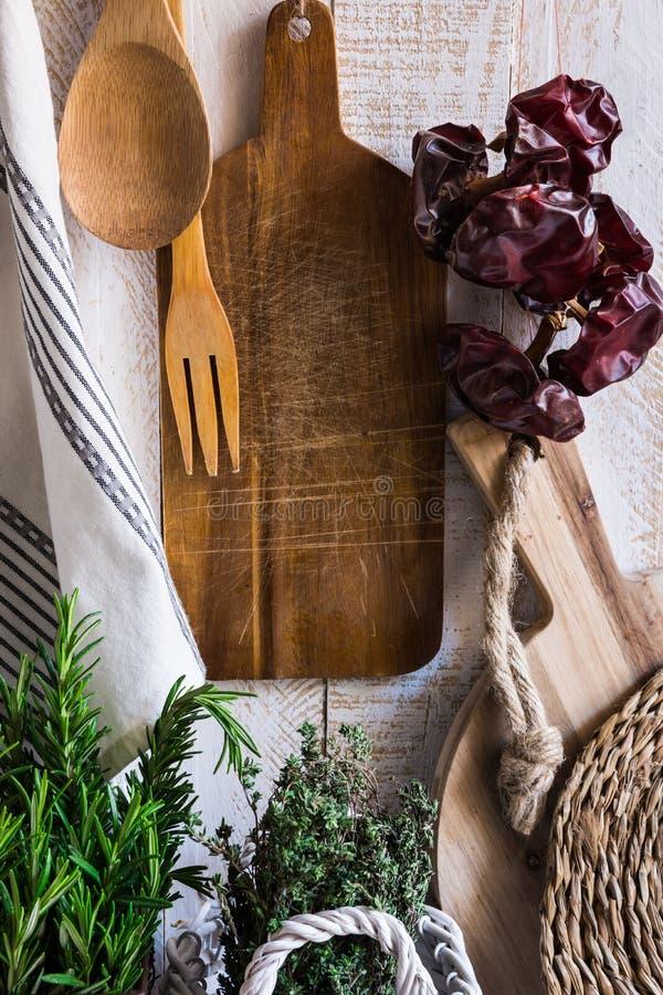 Rustikaler Kücheninnenraum Provence-Art, hölzerne Schneidebretter, hängendes Leinentuch, Schnur mit trockenen Pfeffern lizenzfreie stockfotos