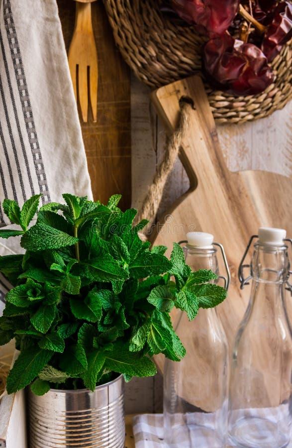 Rustikaler Kücheninnenraum Provence, hölzernes Schneidebrett, Geräte, Glasflaschen, frische Kräuter, Leinentuch auf weißem Hinter stockfotografie