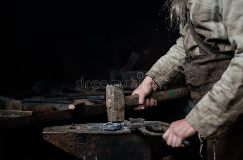 Rustikaler Schmied schmiedet Einzelteil auf dem Ambosse stockfoto