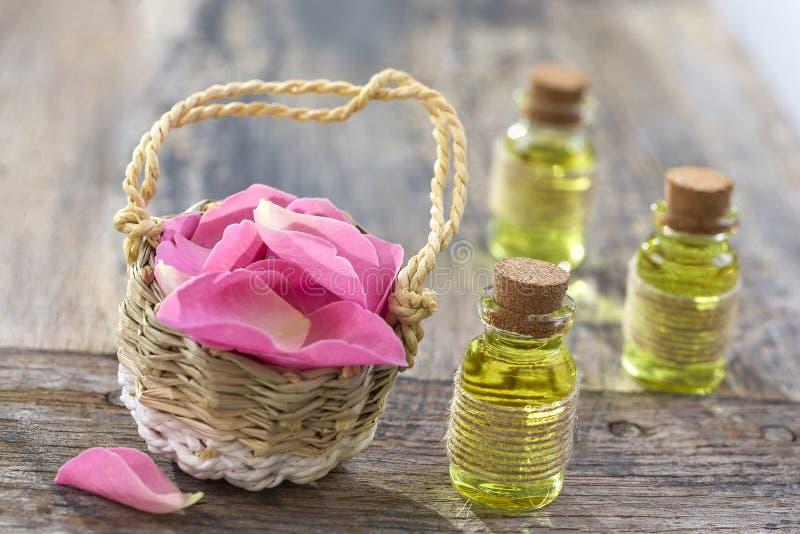 Rustikaler Weidenkorb mit rosa Hagebutteblumen und Flaschen wesentlichem Rosenöl auf hölzernem Hintergrund lizenzfreie stockfotografie