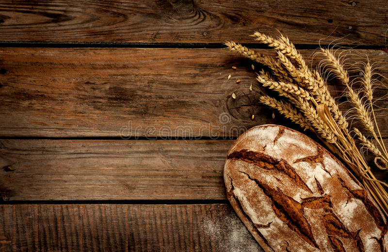 Rustikales Brot und Weizen auf Weinleseholztabelle stockfotos
