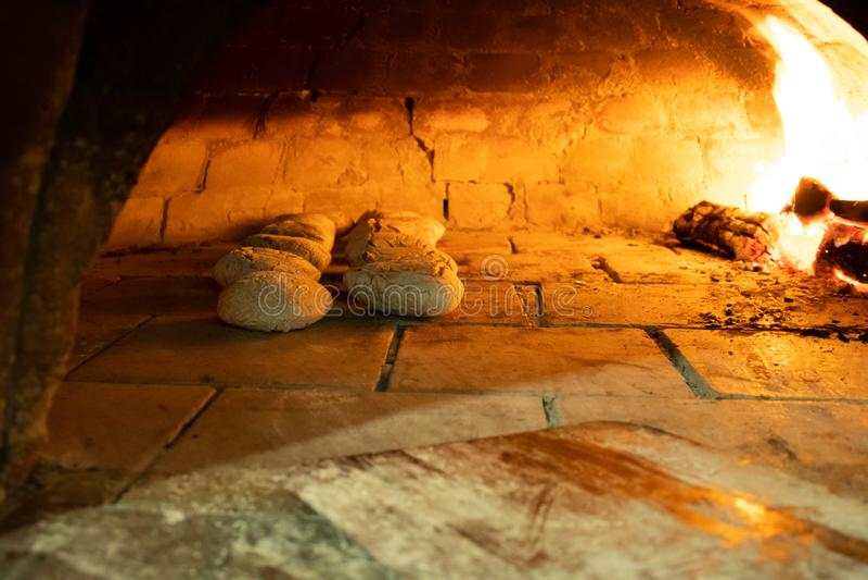 Rustikales Brotbacken im Pizzaofen lizenzfreie stockfotografie