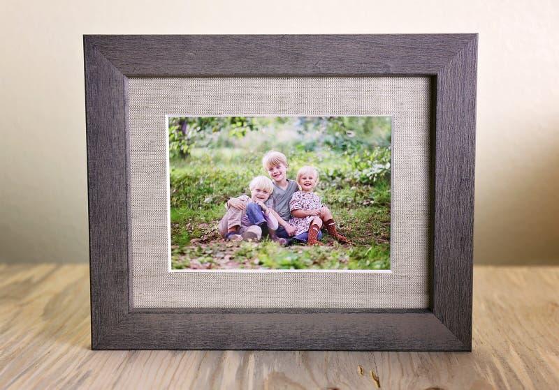 Rustikales Holz gestaltetes Porträt von Kinder Outsid der dreiköpfigen Familie stockfoto
