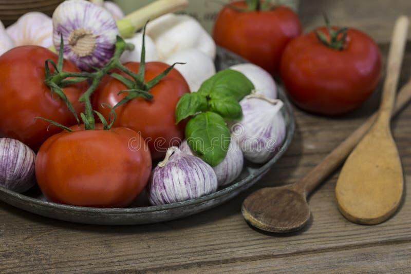 Rustikales Mittelmeerküchestillleben mit Tomaten und Knoblauch stockbilder