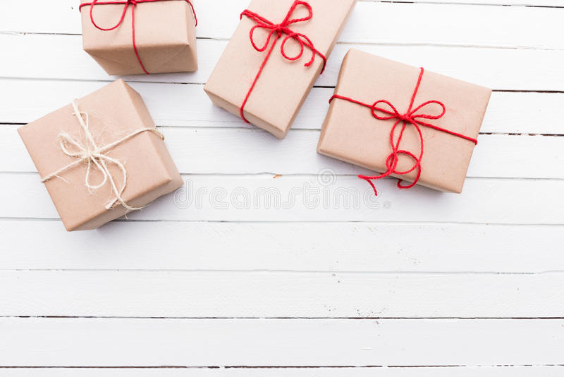 Rustikales Paket des braunen Papiers der Weihnachtsart oben gebunden mit Schnüren Weißer hölzerner Hintergrund lizenzfreie stockfotos