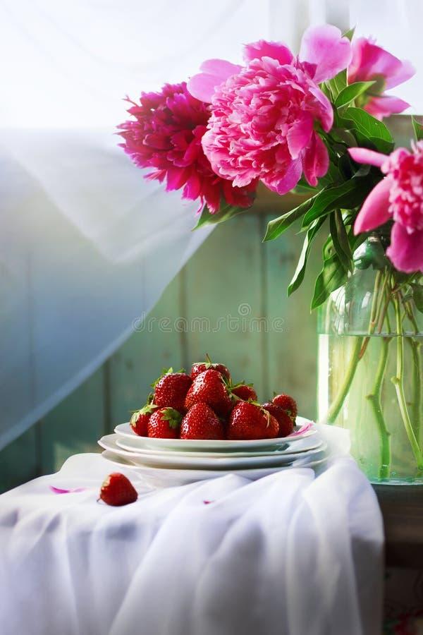 Rustikales Stillleben des Sommers mit Erdbeer- und Pfingstrosenblumenstrauß stockbild