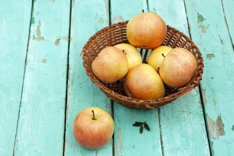 Rustikales Stillleben mit Äpfeln auf Korb auf Türkis verwitterte w stockfoto