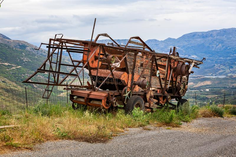 Rusting and decaying combine harvester abandoned on mountain roadside with dramatic mountains behind stock images